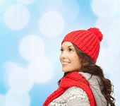 happiness, winter holidays, christmas and people concept - smiling young woman in red hat and scarf over blue lights background