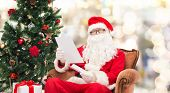 christmas, holidays and people concept - man in costume of santa claus with letter over lights background