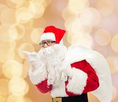 christmas, holidays and people concept - man in costume of santa claus with bag pointing finger over beige lights background
