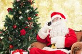 holidays, technology and people concept - man in costume of santa claus with smartphone, presents and christmas tree over yellow lights background