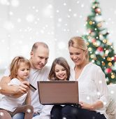 family, holidays, shopping, technology and people - happy family with laptop computer and credit card over living room and christmas tree and snow