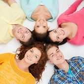 friendship, youth and people - group of smiling teenagers lying on floor in circle
