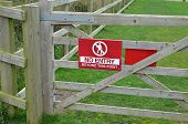 image of no entry  - A red no entry sign attached to a wooden five bar gate - JPG