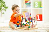 kid boy plays with educational toy indoor