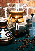 Vintage coffee filter with a wooden holder over a glass jug for brewing fresh coffee alongside a patterned decorative cezve for making Turkish coffee and a metal percolator