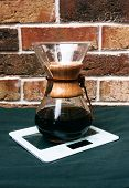 picture of over counter  - Old vintage wooden and glass coffee filter over a glass jug for brewing filter coffee manually standing on a counter in front of a rustic brick wall - JPG