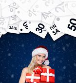 Beautiful lady in Christmas cap holds a set of gifts for friends, wrapped with red paper. Winter sales
