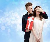 Making a surprise man covers eyes of his pretty girlfriend, blue light background