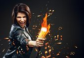 Half-length portrait of female rock musician handing mike on fire, grey background