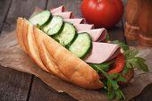 Submarine sandwich with salami, cucumber, tomato and rocket salad