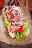 Submarine sandwich with salami, caper, tomato and lettuce salad