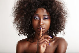 stock photo of shhh  - pretty black woman with a finger on her lips making shhh - JPG