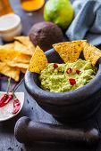 picture of nachos  - black stone bowl with fresh guacamole and nachos for dip - JPG