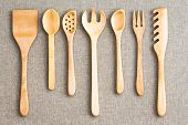 image of neat  - Row of assorted wooden kitchen utensils neatly arranged for size on a neutral beige cloth background viewed from above - JPG