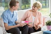 stock photo of give thanks  - Senior woman giving gift her male nurse - JPG