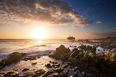 stock photo of shipwreck  - Old shipwreck long exposure on the rocks at sunset - JPG