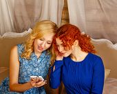 stock photo of sisters  - Two sisters a blonde and a redhead listening to music on headphones - JPG