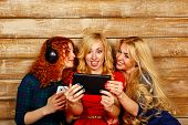 pic of three sisters  - Three sisters blond and red listening to music on headphones - JPG