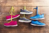 stock photo of wooden fence  - Three pairs of sneakers hang on a nail on a wooden fence background - JPG