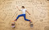 pic of frot  - Cute little boy learning playfully in frot of a big blackboard - JPG
