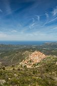 picture of wispy  - The mountain village of Speloncato in the Balagne region of north Corsica with maquis and the Mediterranean in the background against a blue sky and wispy clouds - JPG