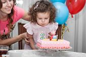 picture of blowing  - Two year old baby girl blows out candles on cake on his birthday her happy mom in the background - JPG