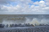 pic of dike  - Storm raging over a lake along a dike through Flevoland in spring - JPG