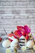 stock photo of figurine  - Small White Rabbit Figurine with Easter Eggs Surrounded by Pink Blossoms on Rustic Wooden Background - JPG