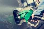 stock photo of fuel economy  - Pumping gas at gas station - JPG