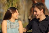 stock photo of conversation  - Friends or couple laughing and taking a conversation sitting on a bench in a park - JPG