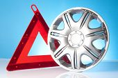 stock photo of alloy  - shiny alloy wheel with road emergency items - JPG