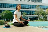 pic of knee  - Young stressed hispanic business woman doing yoga outside office building sitting in lotus position with hands on knees in the street - JPG