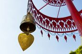 pic of windchime  - brass bell hanging from traditional metal umbrella - JPG