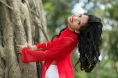 stock photo of bend over  - Charming Vietnamese woman bending over a large fig tree in a park - JPG