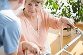 image of disability  - Horizontal view of nurse assisting disabled pensioner - JPG