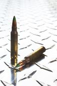 stock photo of cartridge  - Rifle cartridges with green tipped bullets on a shiny piece of armor plate  - JPG