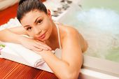 stock photo of hot-tub  - Attractive young woman relaxing in hot tub and looking at camera