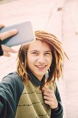 picture of rasta  - portrait of young guy outdoor with rasta hair smiling with smart phone in a lifestyle concept with a warm filter applied - JPG