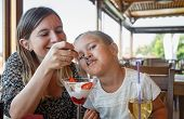 pic of child feeding  - Mom feeds the daughter delicious sweet ice cream with strawberries in a restaurant - JPG