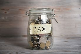 image of emergency light  - Coins in glass money jar with tax label - JPG
