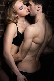stock photo of half  - Erotic play of sexy young couple half naked young man holding blond beautiful girl in black lingerie - JPG