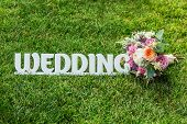 Постер, плакат: The Word Wedding With Beautifull Wedding Bouquet On A Grass