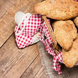 stock photo of bakeshop  - Freshly baked grain bread with sesame in a wicker basket and two rag hearts on burlap napkin - JPG