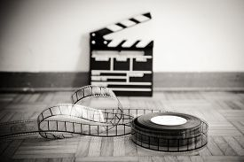 picture of mm  - 35 mm cinema film reel and out of focus movie clapper board in background on wooden floor in vintage black and white - JPG