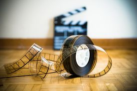 stock photo of mm  - 35 mm cinema film reel and out of focus movie clapper board in background on wooden floor - JPG