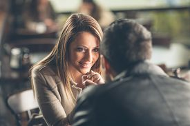 picture of flirt  - Romantic young couple dating and flirting at the bar staring at each other - JPG