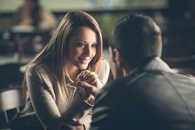 image of flirty  - Romantic young couple dating and flirting at the bar staring at each other