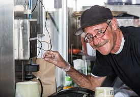 image of food truck  - Smiling worker with order from inside food truck - JPG