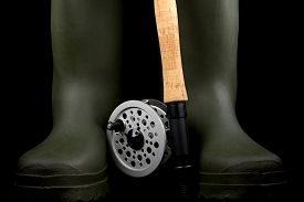 stock photo of fly rod  - Traditional fly fishing rod and reel with green rubber wading boots against a black background - JPG