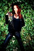 red hair fashion woman in black with fashion accessories against wall with green rambler plant